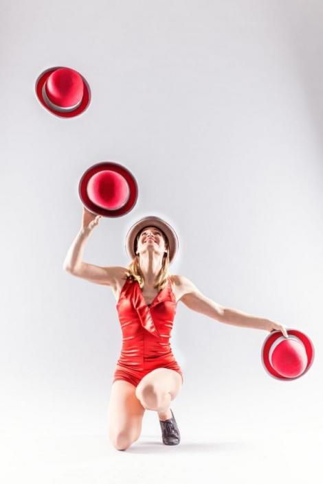 Artistin jongliert mit roten Hüten