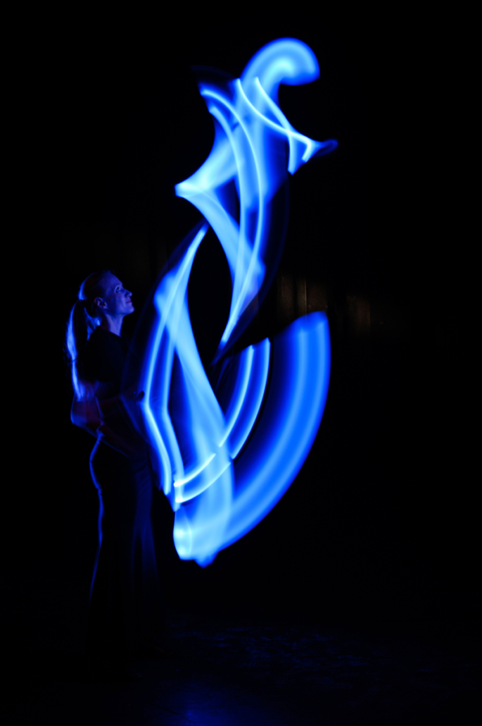Jongleurin mit blau leuchtenden LED Keulen