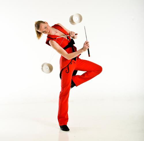 Frau in rotem Kostüm jongliert mit zwei Diabolos in tänzerischer Pose